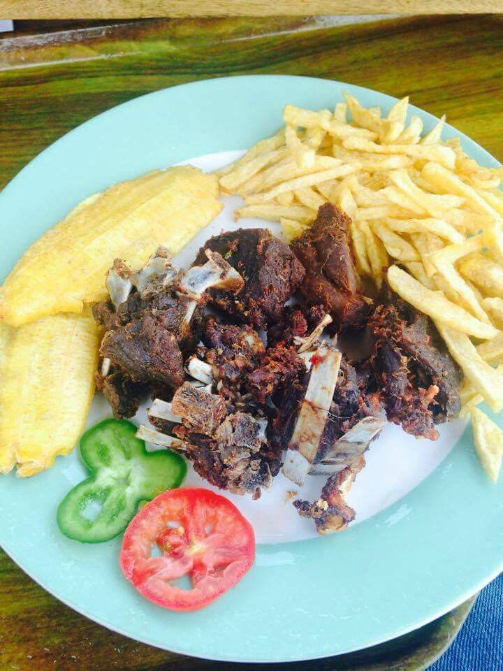 Fried goat meat with fried plantain and french fries
