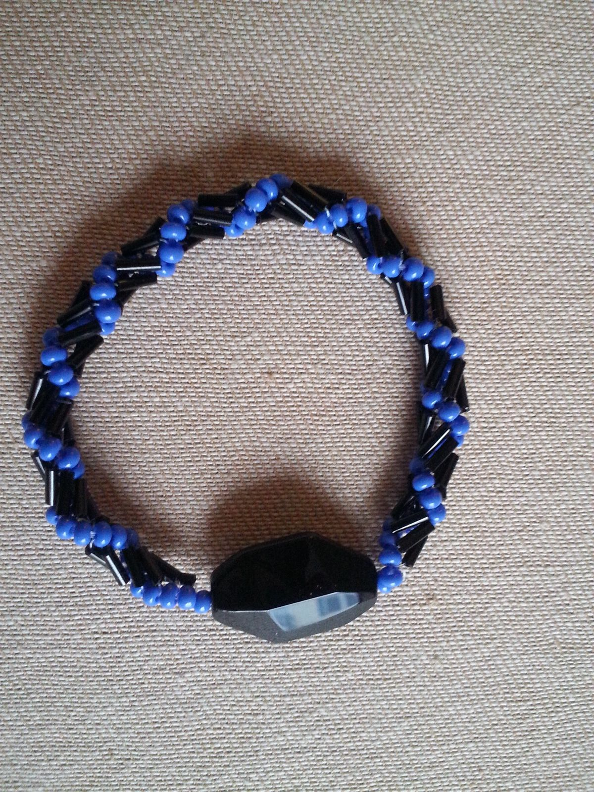 black bugle bead spiral bracelet with bright blue glass beads and large black glass focal bead. The spiral stitch has just enough stretch