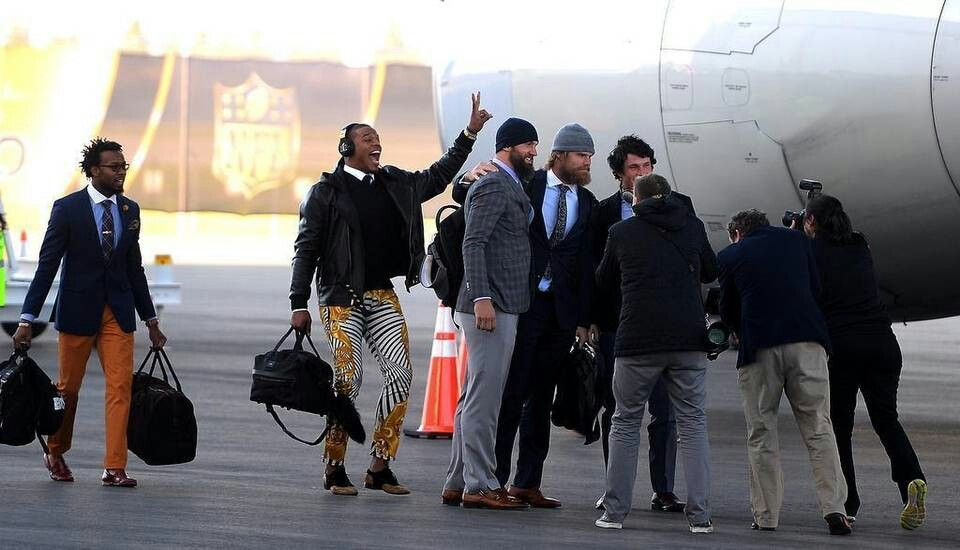Cam Newton photobombs Derek Anderson, Greg Olsen, and Luke Kuechly as Josh Norman walks by at the Mineta San Jose International Airport on Sunday 1/31/16