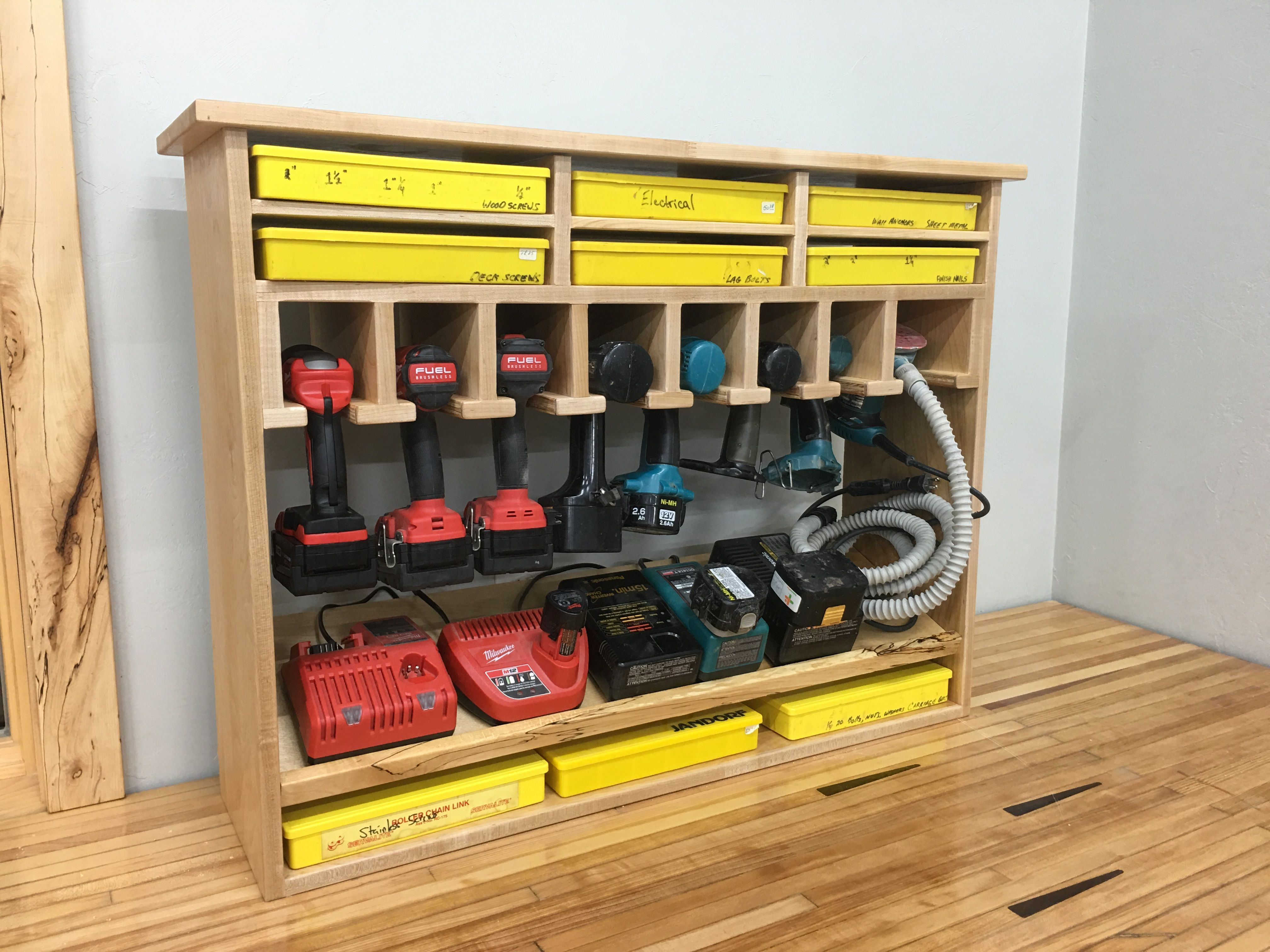 "Cordless Tool Station and screw storage.  This shelf holds 7-8 drills and 1 sander.  I added a few screw bins for convenience and the angled shelf makes for a perfect spot to hide all the cords. ~30""x36"""