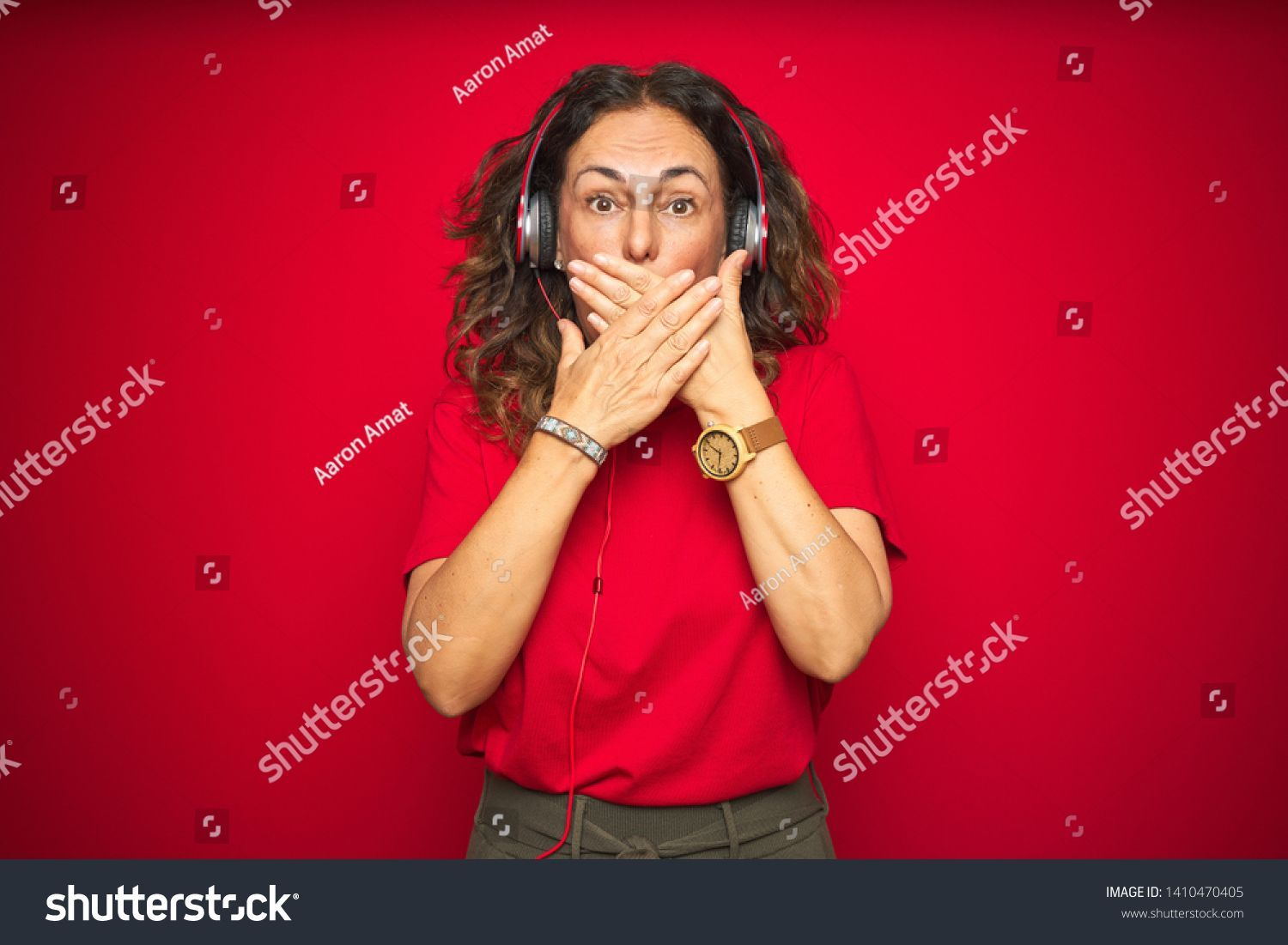 Middle age senior woman wearing headphones listening to music over red isolated