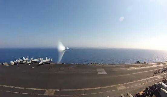 F-18 Hornet breaking the sounds barrier while flying by an aircraft carrier.