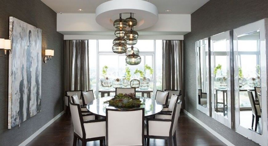 This beautiful dining room brightens up the dark color of the walls and floor with white upholstered chairs, large reflective mirrors, and white ceiling features. The gorgeous chandelier features round glass globes that float like bubbles in the air.