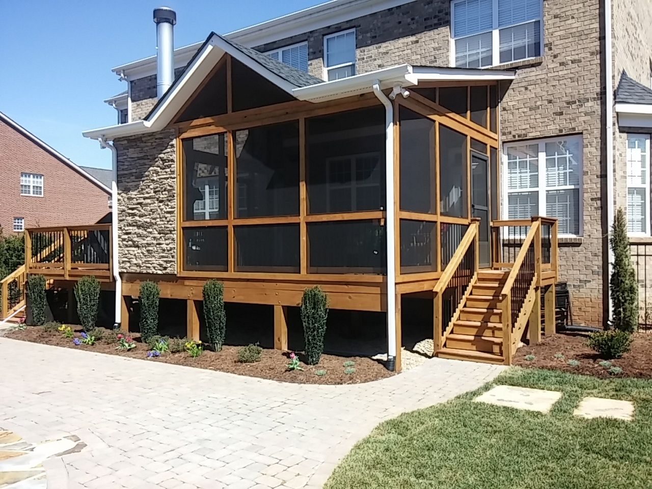 Screen Porch With Integrated Outdoor Fireplace And Paver