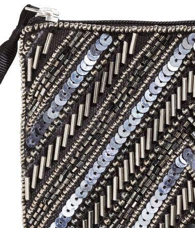 En liten clutch i canvas med pärl- och paljettbroderier på framsidan. Dragkedja upptill. Fodrad. Storlek 11x13,5 cm.