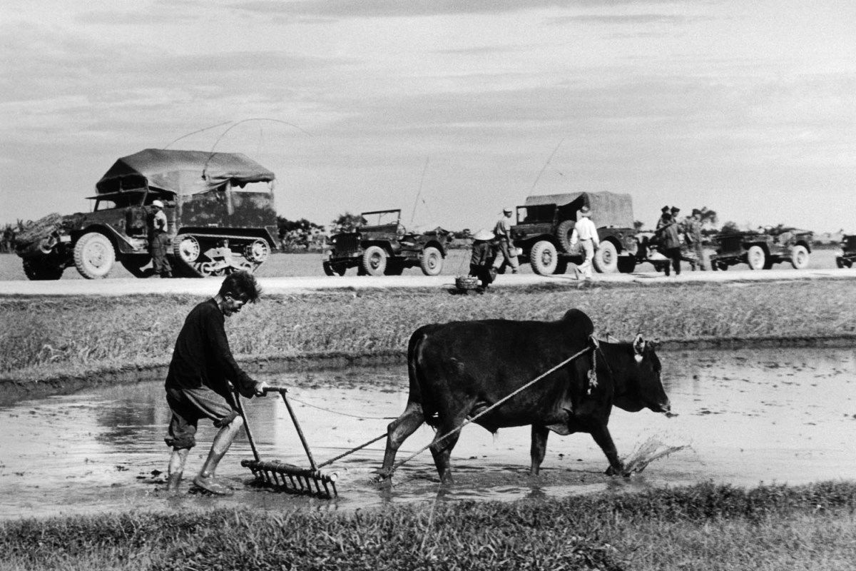 Robert Capa, A French military convoy marches past a rice field on its way north towards Doai Tan, Vietnam, May 25, 1954.
