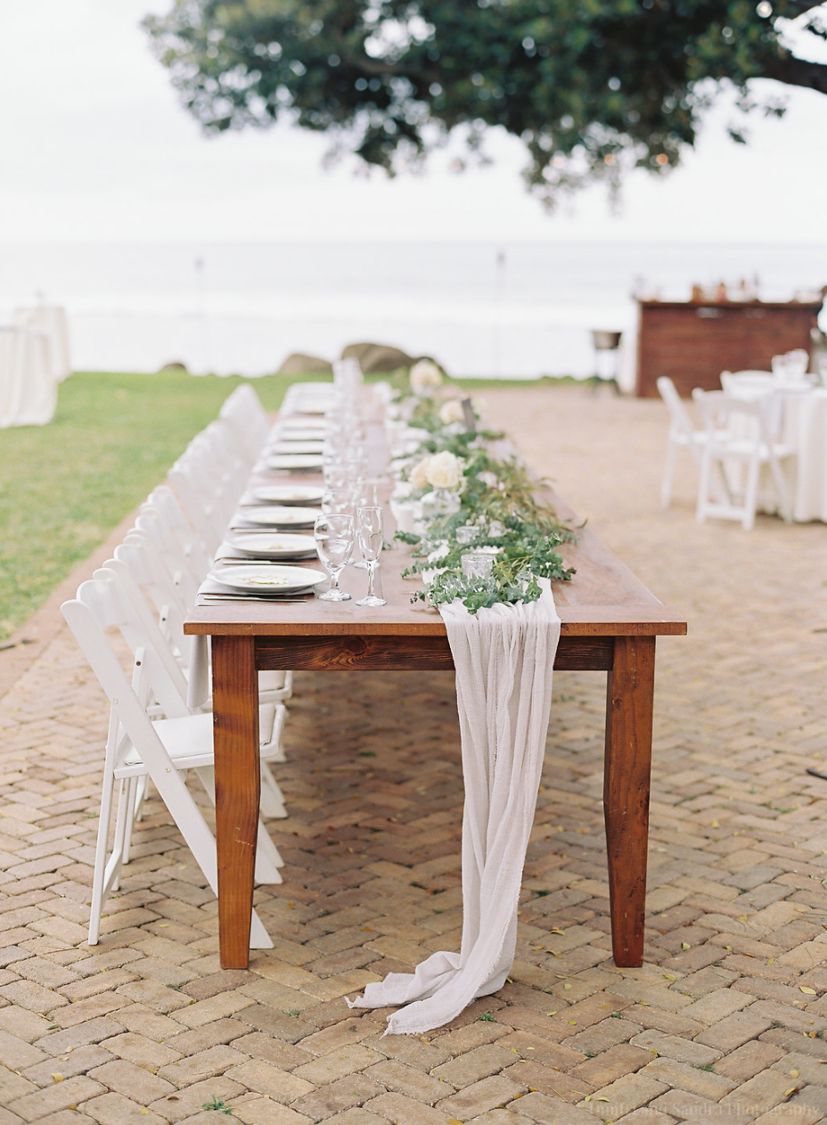 Farm Wood Head Table With Adorn Runner Eucalyptus Garland And White Folding Chairs Head Table Wedding White Chairs Wedding Wedding Chairs