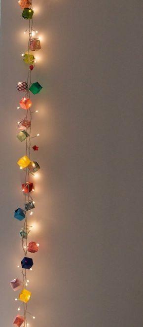 En lugar de colocar las luces en las cajas, puedes simplemente entrelazarlas con una guirnalda de cajas de origami.