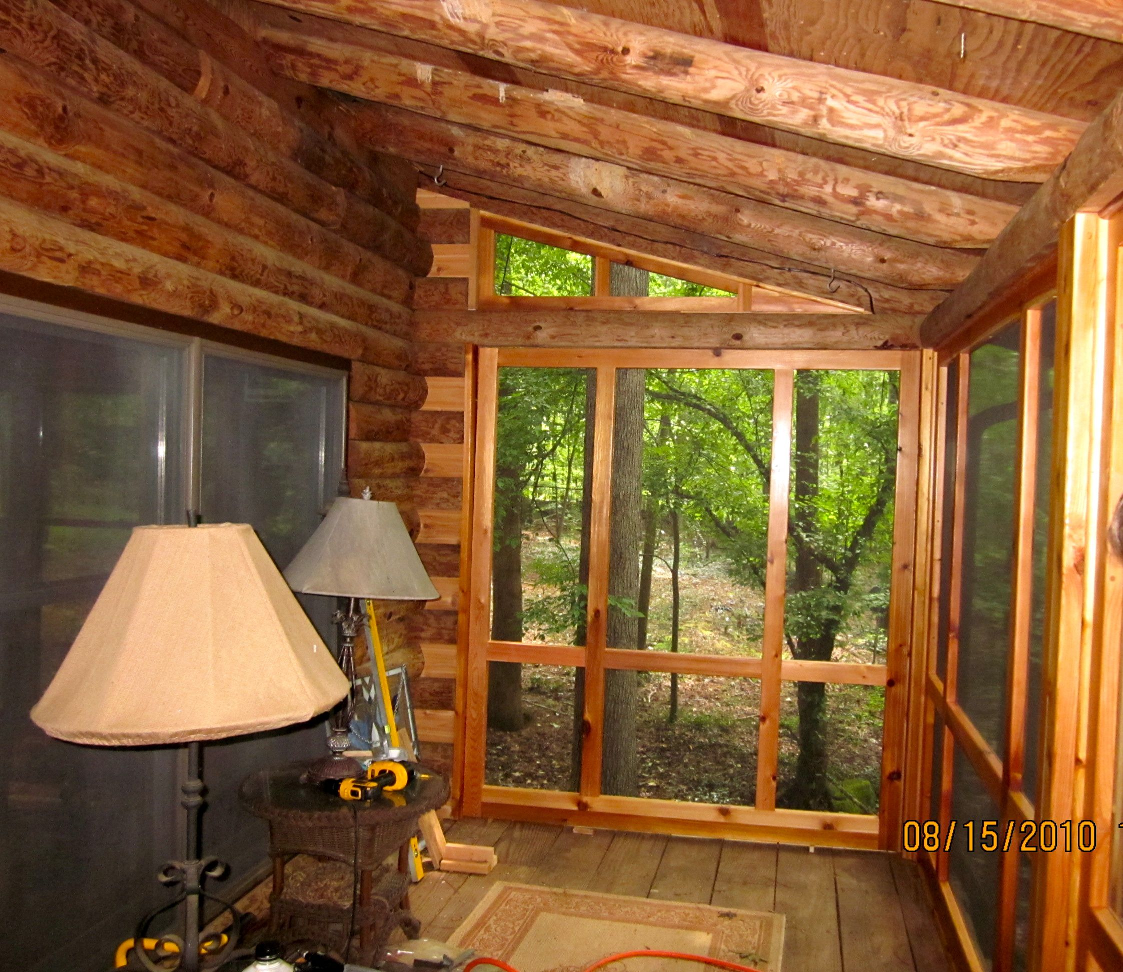 beautiful screened in porch added to a log cabin porch