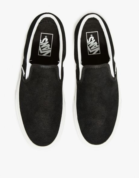 a8b405899b1d7f Classic slip-ons in black leather from Vans with allover Black Lizard  texture. Features low top construction