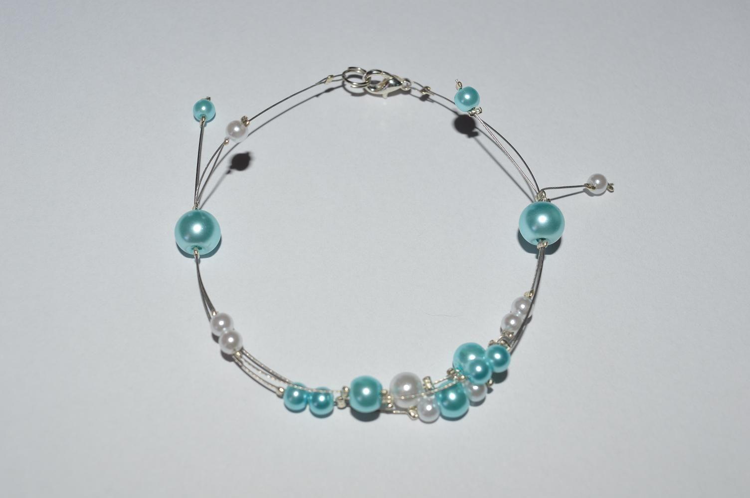 Ce bracelet est réalisé sur du fil d'acier argenté solide et souple.  Il est composé de perle de verre nacrée turquoise de 4 et 6 mm et nacrée blanche de 4 et 6 mm .  Le motif principal est monté sur trois fils câblés parsemés de perles turquoise et blanche avec une alternance de taille. A chaque extrémité de la perle de 8mm turquoise , des fils s'échappent pour s'achever sur des perles de 3 mm.   Le bracelet mesure 19 cm.  Les magniques perles de ce bracelet sont idéales pour toutes vos…