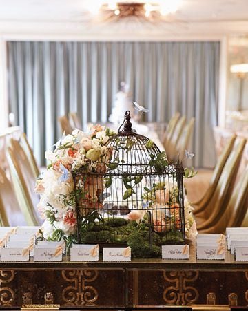 a vintage birdcage covered in the seasons prettiest blooms makes an unexpected focal point on an escort card table
