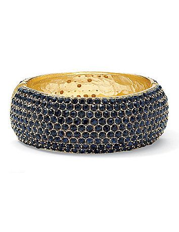 "Go from bland to glam instantly with this navy blue multi-crystal bangle bracelet. Encrusted in sparkling crystals, it's the epitome of high shimmer and shine. 27 mm width. With magnetic closure. 8 1/2"" length. 14k gold-plated. catherines.com"