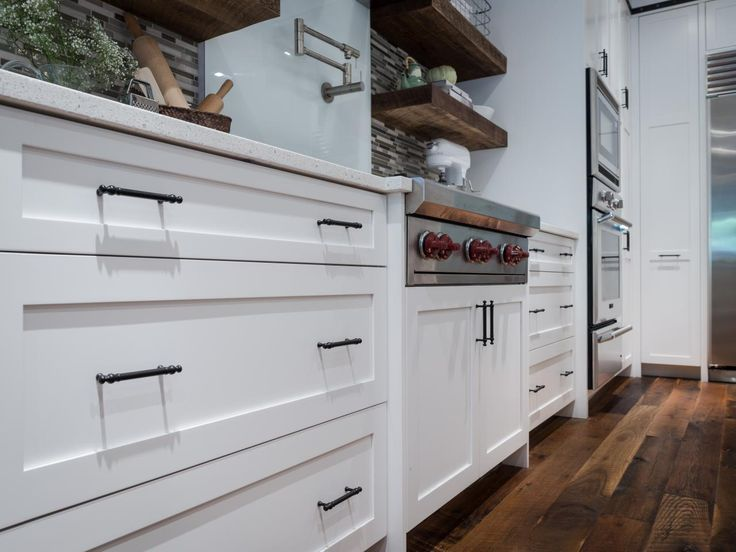 White shaker style cabinetry is trimmed with delicate for Kitchen cabinets vs drawers
