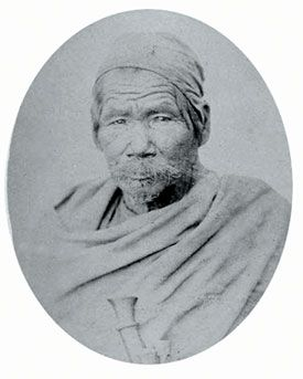 Picture of a Magar elder with wrap-around shawl and a 'Himali' topi.