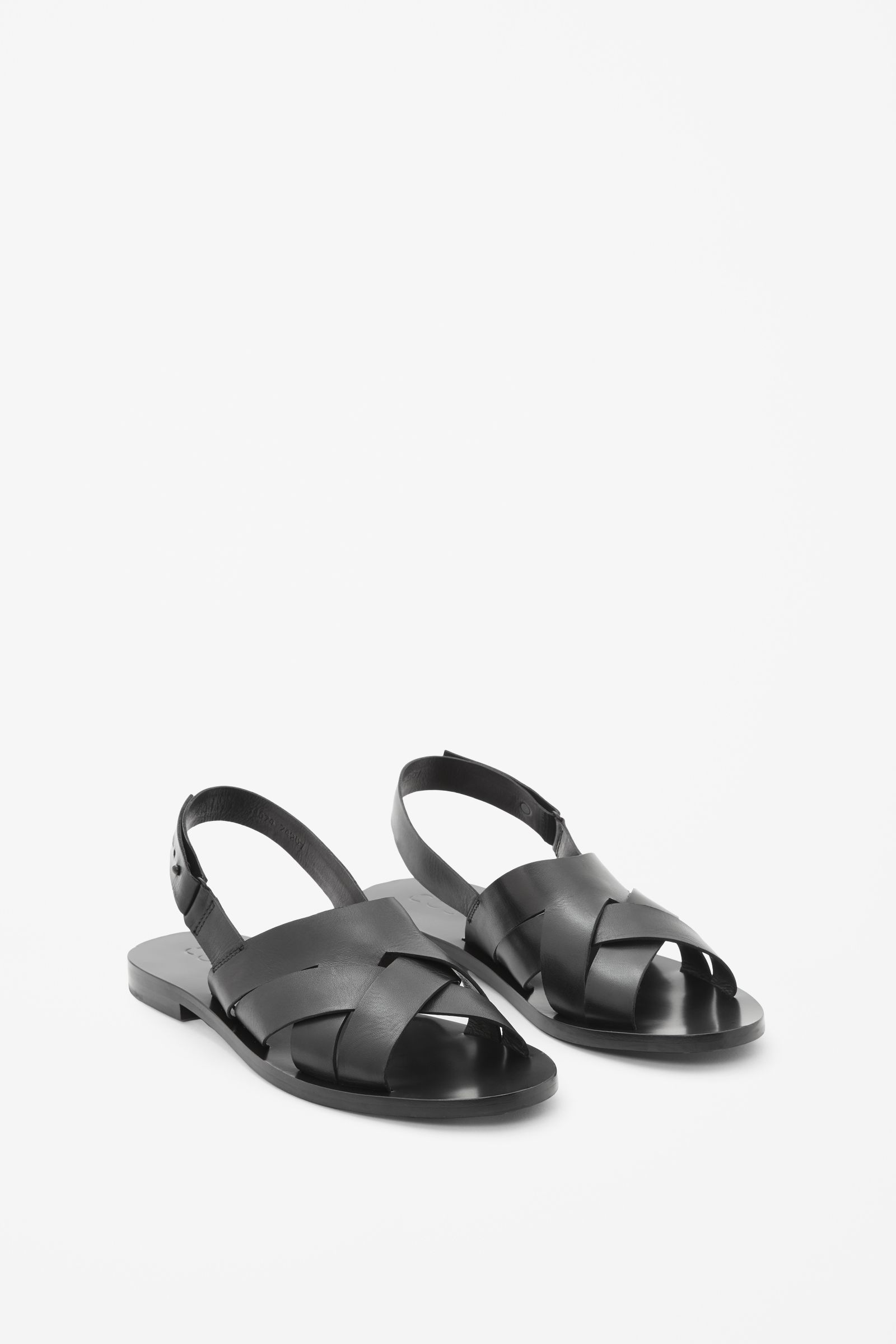 These sandals are made from braided panels of soft, buttery leather. A casual style, they are completed with a stacked wooden heel and a modern metal pin fastening.