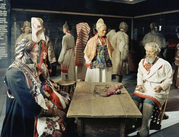 suomalais-ugrilaisia pukuja: kirjottuihin vaatteisiin puettuja nukkeja istumassa ja seisomassa puupöydän ympärillä. Kuva: Matti Huuhka (2005)