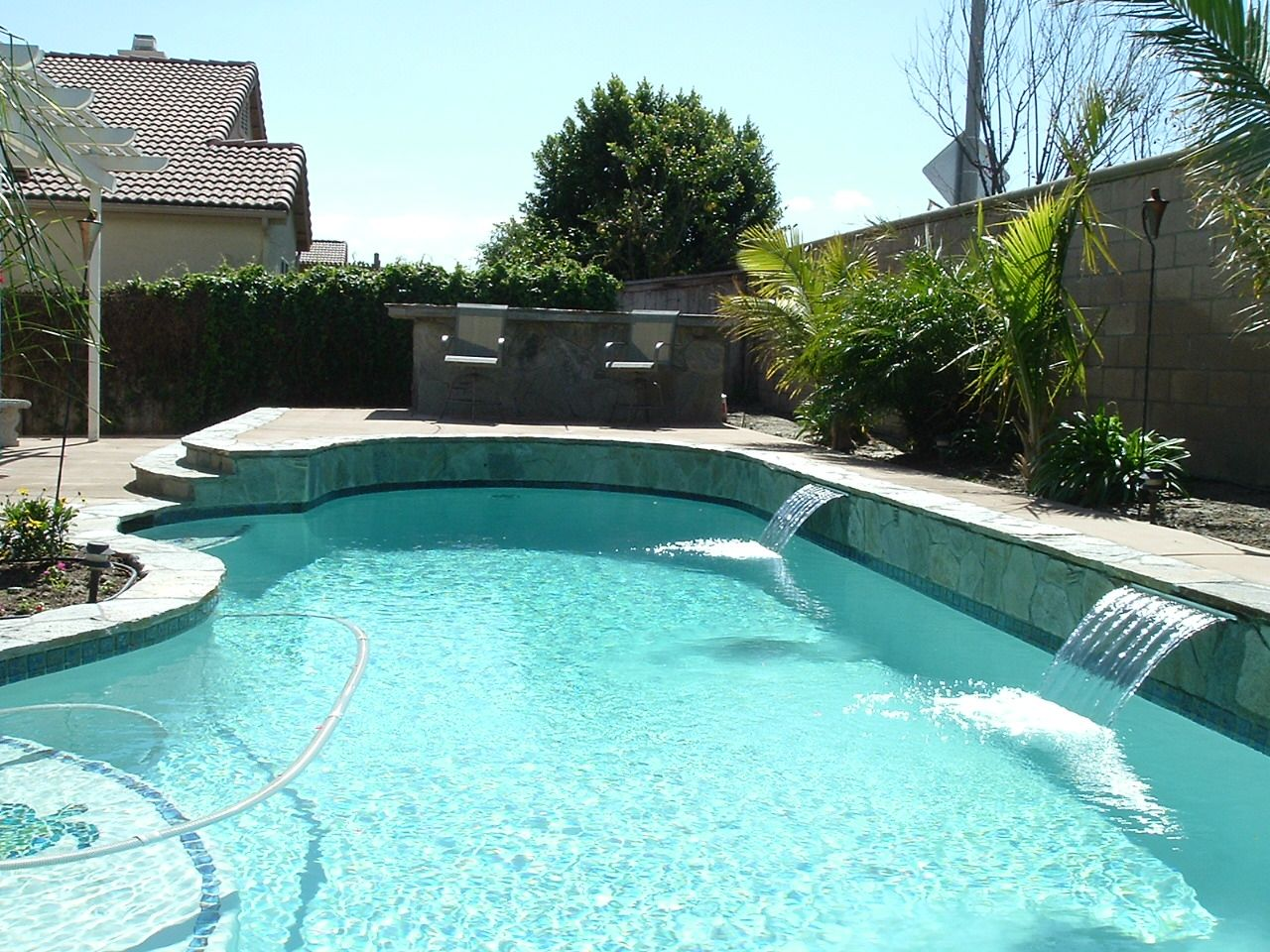 beautifully enticing pool and landscaping complimented by a bbq