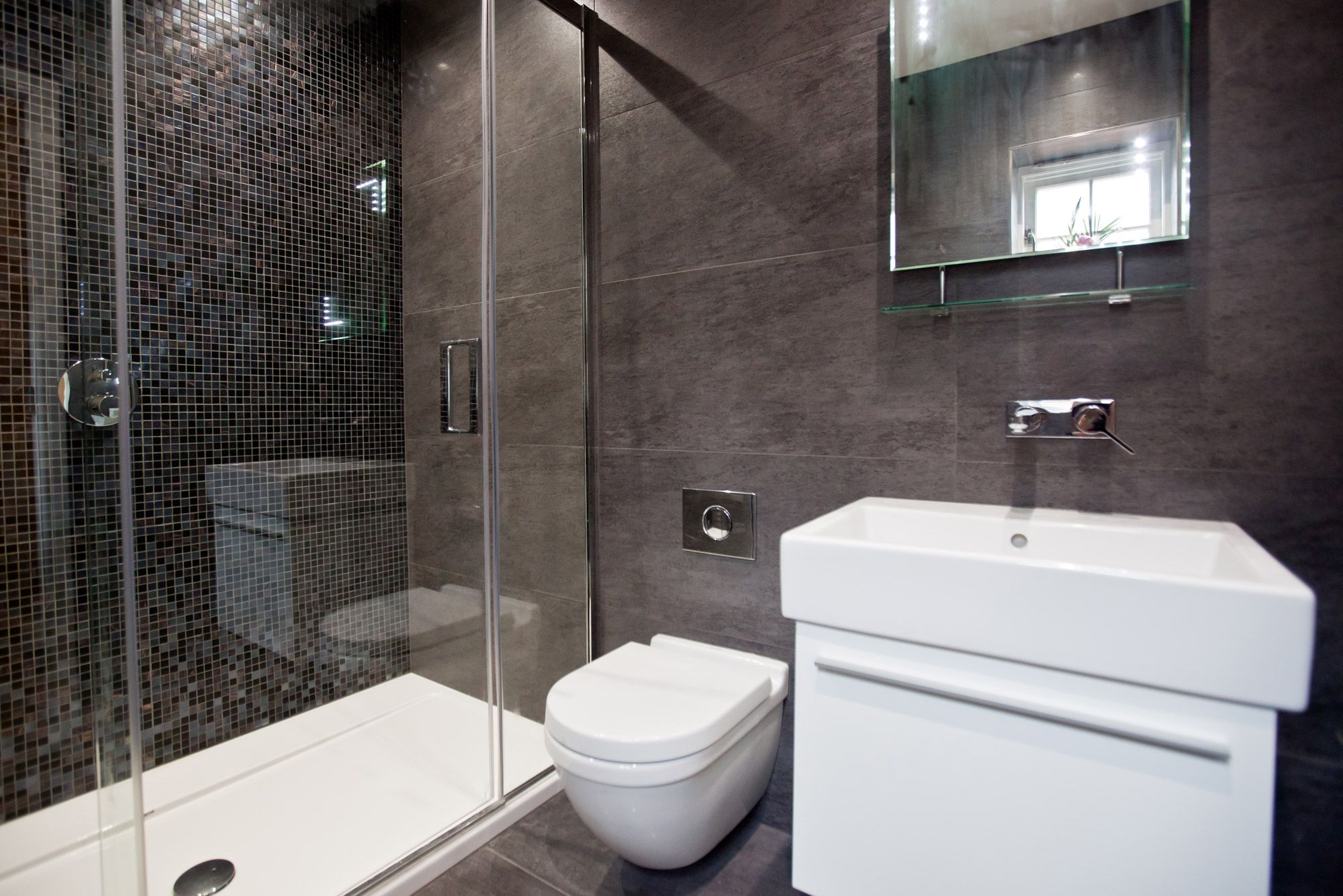 Black ensuite with large floor and ceiling tiles and black mosaics black ensuite with large floor and ceiling tiles and black mosaics creating a feature wall dailygadgetfo Gallery