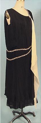 c. 1924 JEAN MAGNIN, Paris Black Georgette Knife-Pleated Flapper Dress with Rhinestone Trim and Long Attached Scarf. The entire dress have vertical knife pleats, and there is a band of rhinestones twice encircling the dress, and then ending front and back on a rhinestone diamond. The dress is also two-tiered at the very bottom, for a bit of extra detailing. The long ecru chiffon scarf is attached all the way down. Sideway