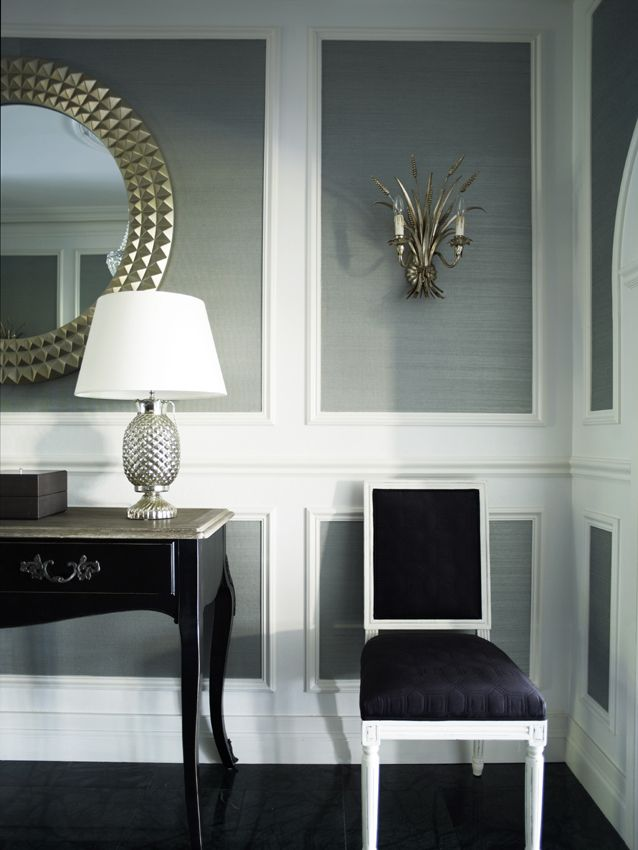 Extra wide moldings that frame warm gray grasscloth is a