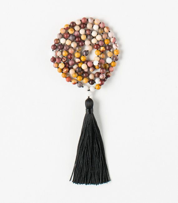 108 Mookait Jasper beads Tibetan Buddhist Mala with White Onyx  Use I am Powerful Mookaite Jasper Mala to connect with elemental Earth powers for increasing self-confidence, self-worth and to realise your full potential.  Jasper is believed to provide harmony and increase creativity.  Onyx, representing the Earth element, its also known for balancing male and female polarity and increasing hormonal balance. The black stone is said to help with objectivity and making intelligent decisions…
