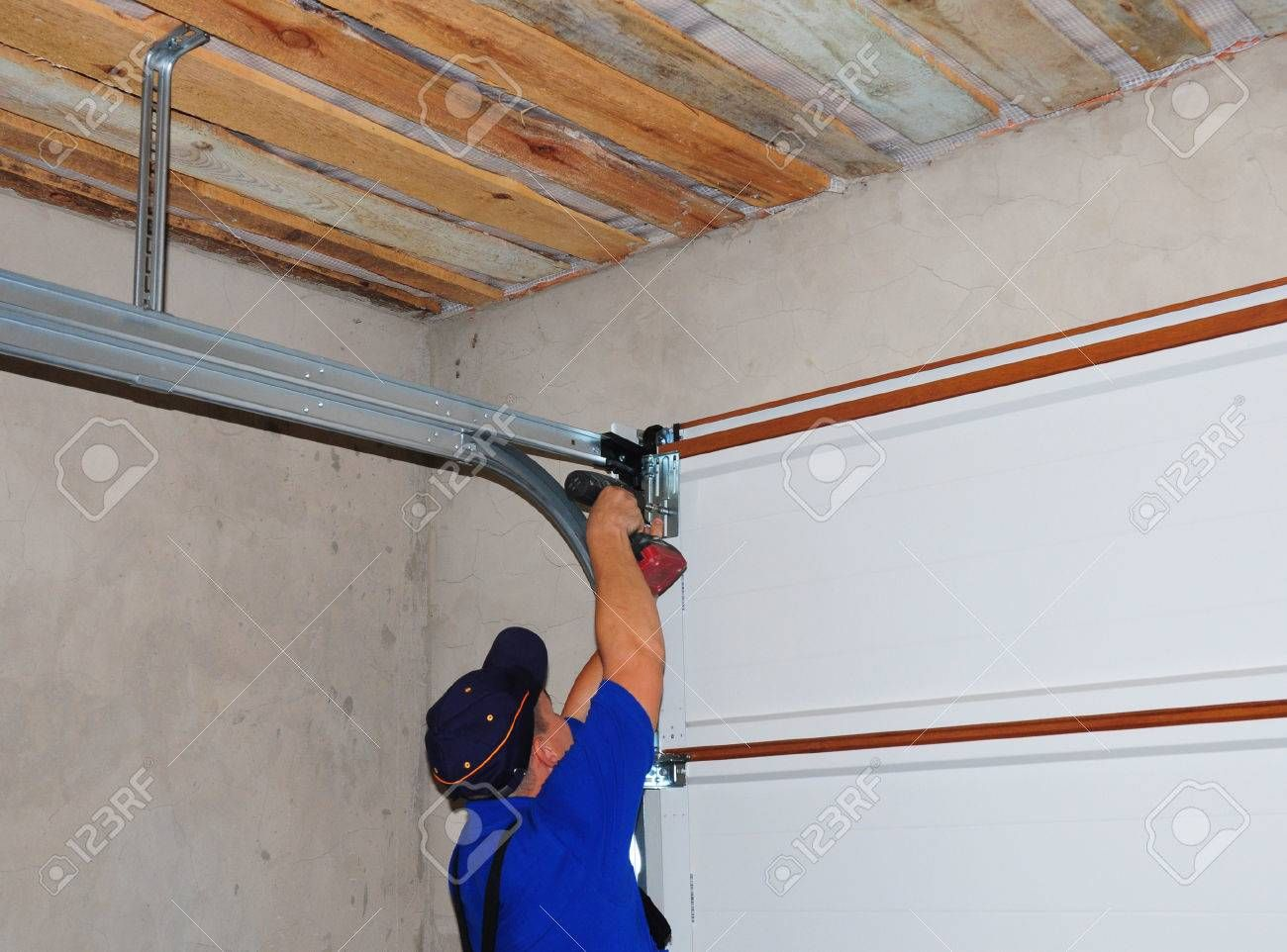 Contractor Installing Garage Door Post Rail And Spring Installation And Garage Ceiling Spring Tensio Door Repair Garage Door Spring Repair Garage Door Springs