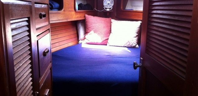 Side storage in V-berth with head of bed at the point.