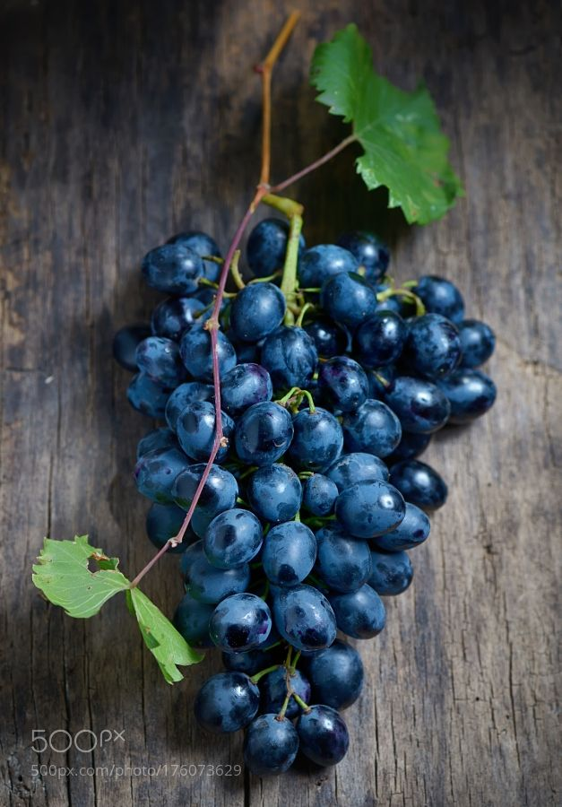 Bunch of red grapes on wooden background by jordachelr