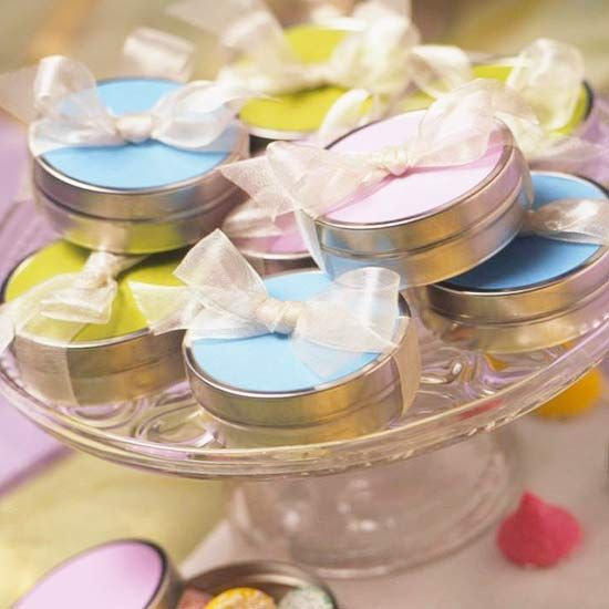 Pastel Candy Tin Favors.          This pretty pastel display looks good enough to eat. Fill small tin canisters found at a crafts store with colorful soft candies. Glue color-coordinated cardstock circles to the tops of the canisters, and tie with sheer ribbon to add a delicate touch. Display on a cake platter to create an unexpected birthday party centerpiece and make it easy for guests to pick up their party favors on their way out.