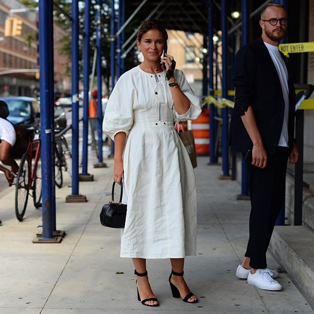 Black and white is always right: Miroslava Duma @miraduma in a white dress with black accessories at the Gabriella Hearst presentation today. Photo by @gastrochic #NYFW #fashion #streetstyle