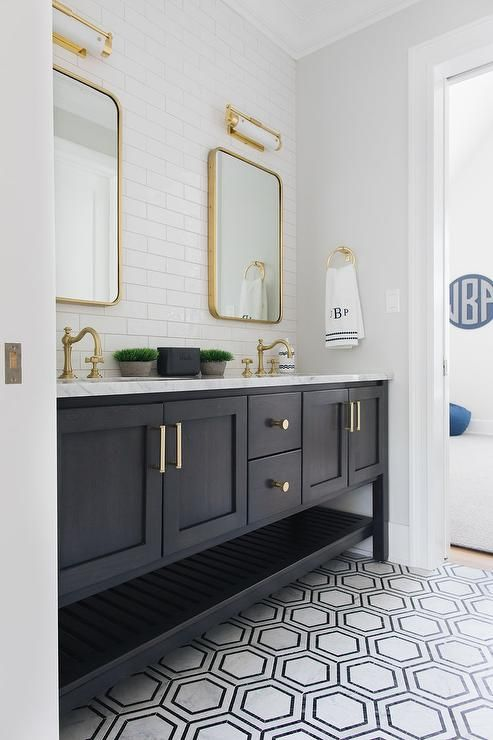 Black and gray marble floor tiles lead to a black wooden dual bath vanity boasting a slatted shelf and a white marble countertop holding antique brass. #blackwhitebathrooms