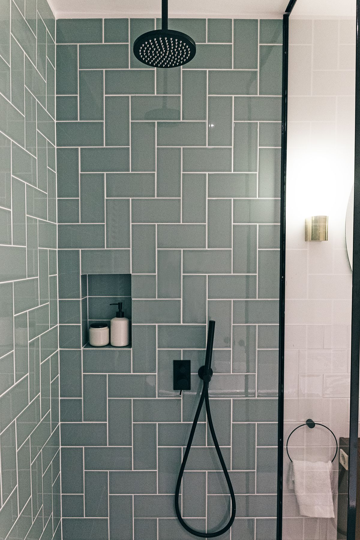 Contemporary bathroom with black faucets, tiles in a herringbone ...