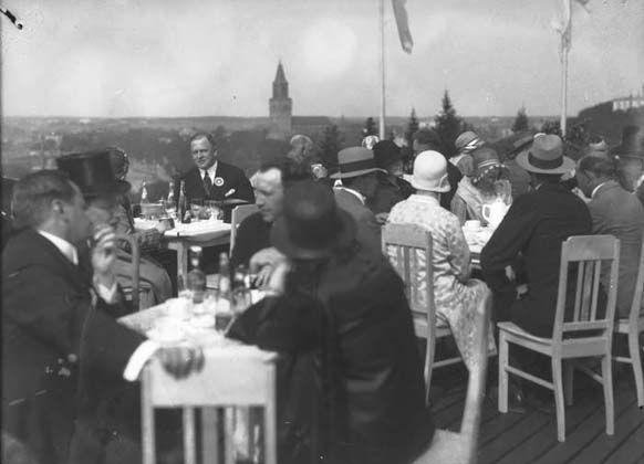 Hattupäisiä herroja ja rouvia, Turun messujen messuvieraita, istuu seurustelemassa ulkoilmaravintolassa Samppalinnanmäellä vuonna 1929. Noihin aikoihin päti kirjoittamaton sääntö, jonka mukaan turkulaisiin ulkoilmaravintolohin tervetullutta oli vain herrasväki, ja muut kaupunkilaiset saivat pysytellä puistojen liepeillä.  Pyöreä, kolmikerroksinen messuravintola oli 700-paikkainen ja sen kattoterassilta aukesi upea näköala.  kuva TS 1929.