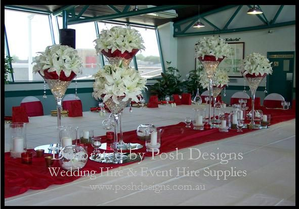 Red organza sashes, white lycra chair covers, white tablecloths, red runners, tall martini vase table centres with oriental lilies, candles and mirrored tiles all for hire. Australia wide. Visit www.poshdesigns.com.au for more photos and info, or email lisa@poshdesigns.com.au for pricing packages