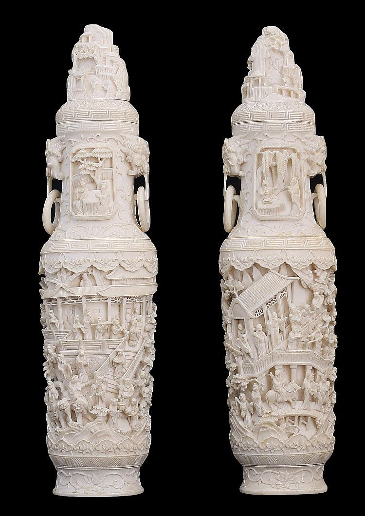 PAIR OF CHINESE CARVED IVORY VASES AND COVERS, intricately carved in low relief depicting continuous village scenes, flanked by mythological mask handles suspending loose rings, and the covers each surmounted by miniature mountains. Height 10 in.