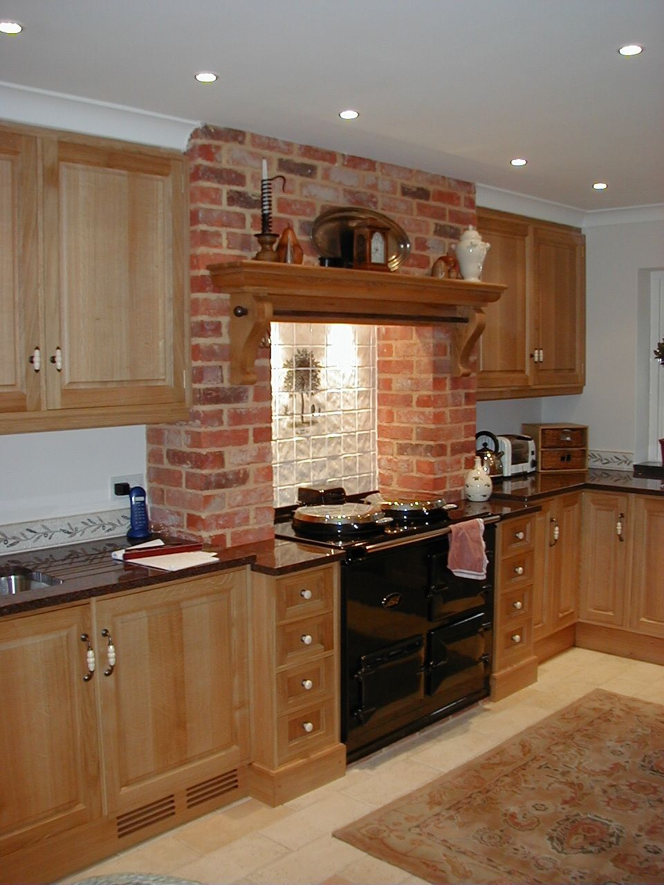 A Quintessential Country Kitchen. Oak Cabinets With A Large Mantel Over The Range  Cooker.