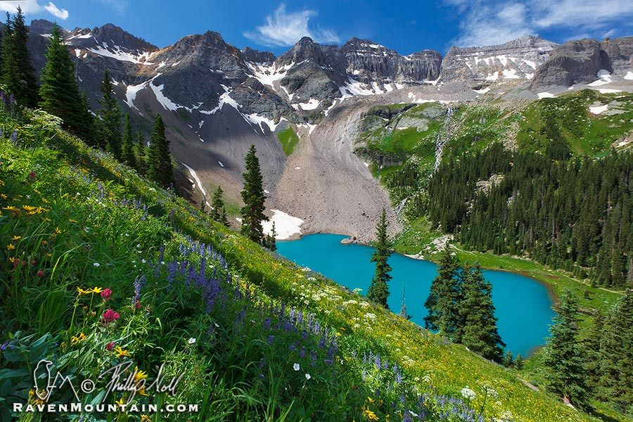 "Blue Lake photo - High up in the Mount Sneffels Wilderness lies three aquamarine jewels, set in gray mountains and green meadows. This is the lowest of the tree ""Blue Lakes"" in what can only be described as an idyllic setting. The hillsides are covered in wildflowers of every color, waterfalls cascade down to the lake from the snowfields above, and an evergreen forest sits at the edge of the lake. Lower Blue Lake, San Juan Mountains, Colorado."