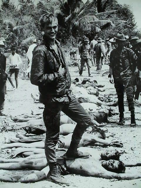 January 1968 - U.S. soldier posing with dead Viet Cong during the Tet offensive.