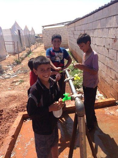 Syrische vluchtelingenkinderen spelend bij een waterpunt.