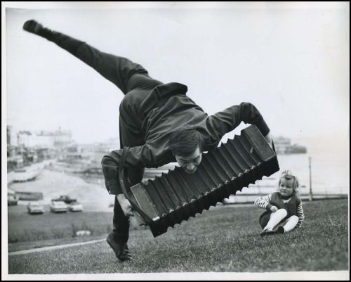 """alfiusdebux: """"Acrobatic accordion player serenading a somewhat uncertain little girl on the grass. Photography dated 3-24-1970. """""""