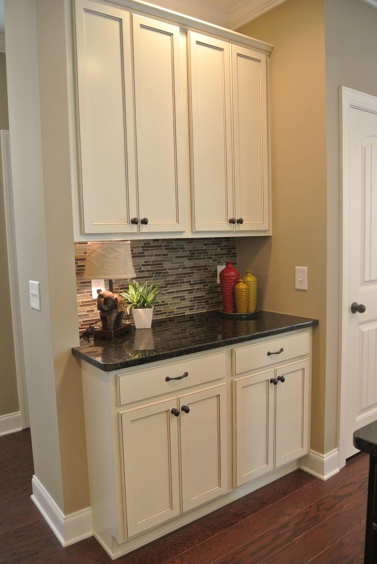 glazed white cabinets, gray glass tiles, and dark granite ...