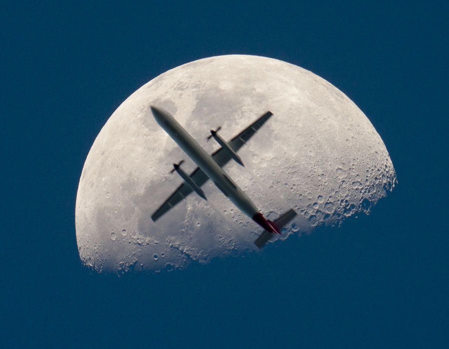 Airplane in front of the moon