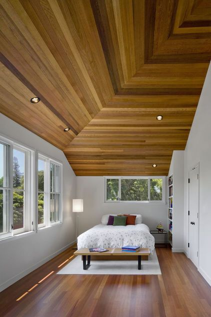 The red cedar ceiling uses a tongue and groove assembly to conceal the nails and a mitered connection at the corner joints as the wood changes direction with the ceiling framing. The ceiling and flooring add visual interest to a sun-drenched, porch-like bedroom on the second floor.