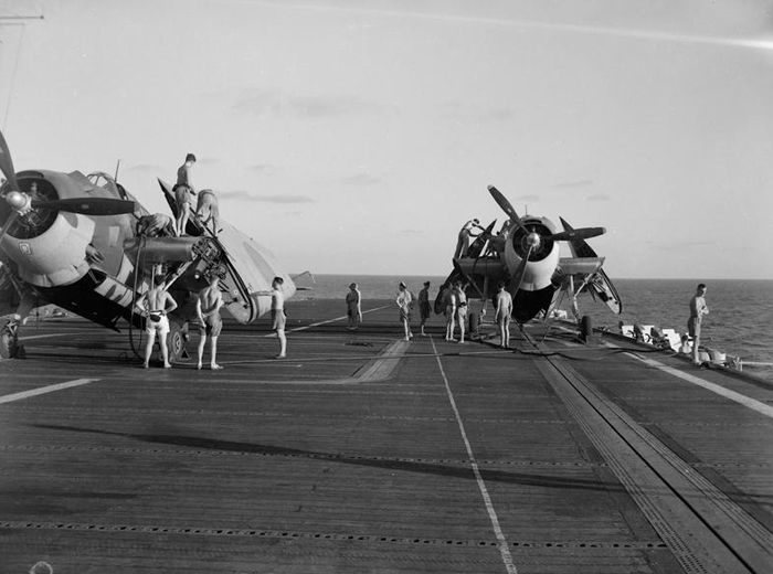 "A calm scene aboard HMS Shah in the Indian Ocean. Two Grumman Avengers (which appear factory fresh) are being refuelled from hoses brought from the catwalk. The Avenger at right is ""stropped"" to the starboard hydraulic catapult. Photo: Imperial War Museum"