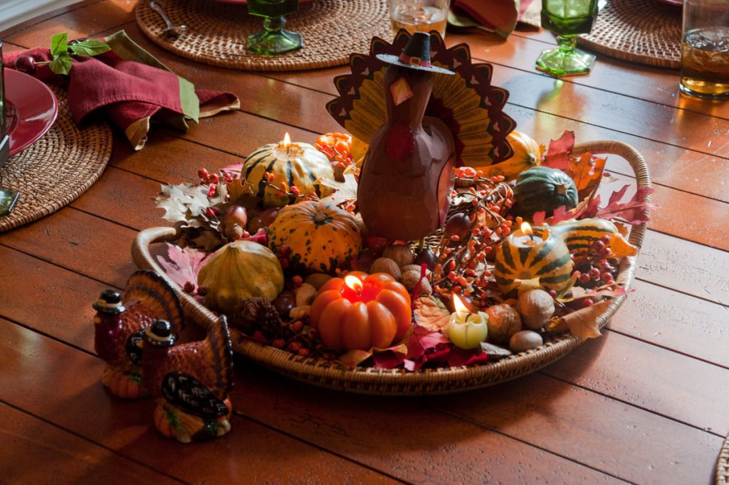Thanksgiving table with candles and a wooden turkey sculpture