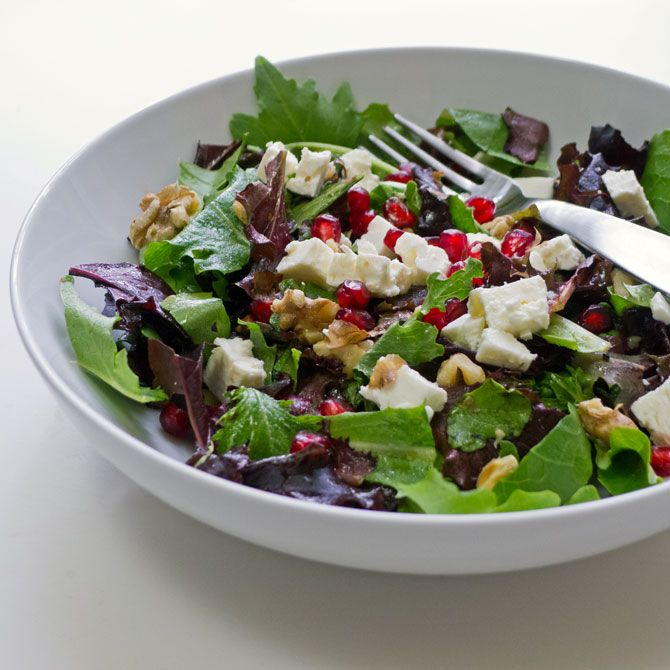 A delicious leafy salad topped with feta cheese, pomegranate seeds and toasted walnuts.