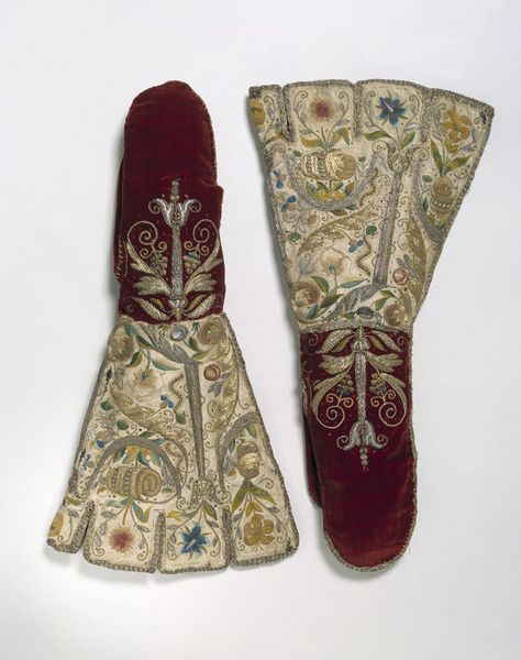 """Pair of Mittens: ca. 1600, English, velvet and satin embroidered with silver and silver-gilt thread, coloured silks, beads and spangles. """"This mitten had a decorative rather than practical function. Like many of the embroidered gloves made during this period, its purpose was to show off the wearer's wealth and status..."""""""