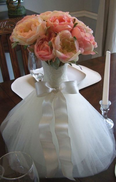 Flowers inside a vase that takes its inspiration from the bridal gown.  See more bridal shower decorations and party ideas at http://www.one-stop-party-ideas.com