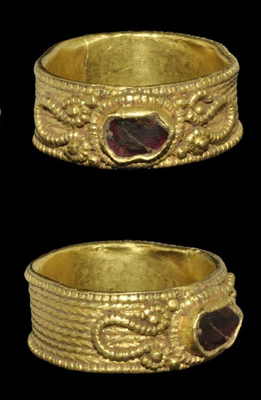 Saxon gold filigree and garnet finger ring, 7th-8th century AD.  A sheet gold finger ring with faux-filigree bands to the outer face, filigree volute scrolls to the shoulders with granule detailing, garnet cloison to the bezel with filigree collar.
